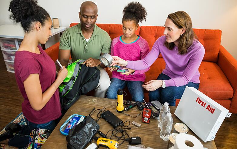 A family creating an emergency supply kit including a first aid kit, a flashlight, toilet paper, canned food and water