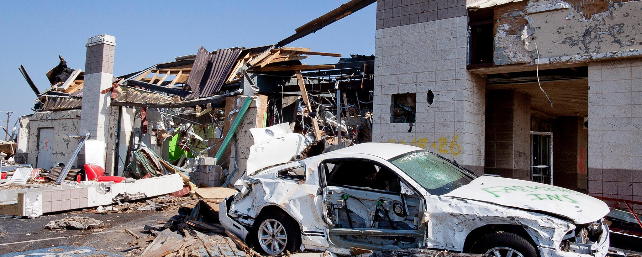 A building destroyed by a hurricane with a white car missing a door due to damage