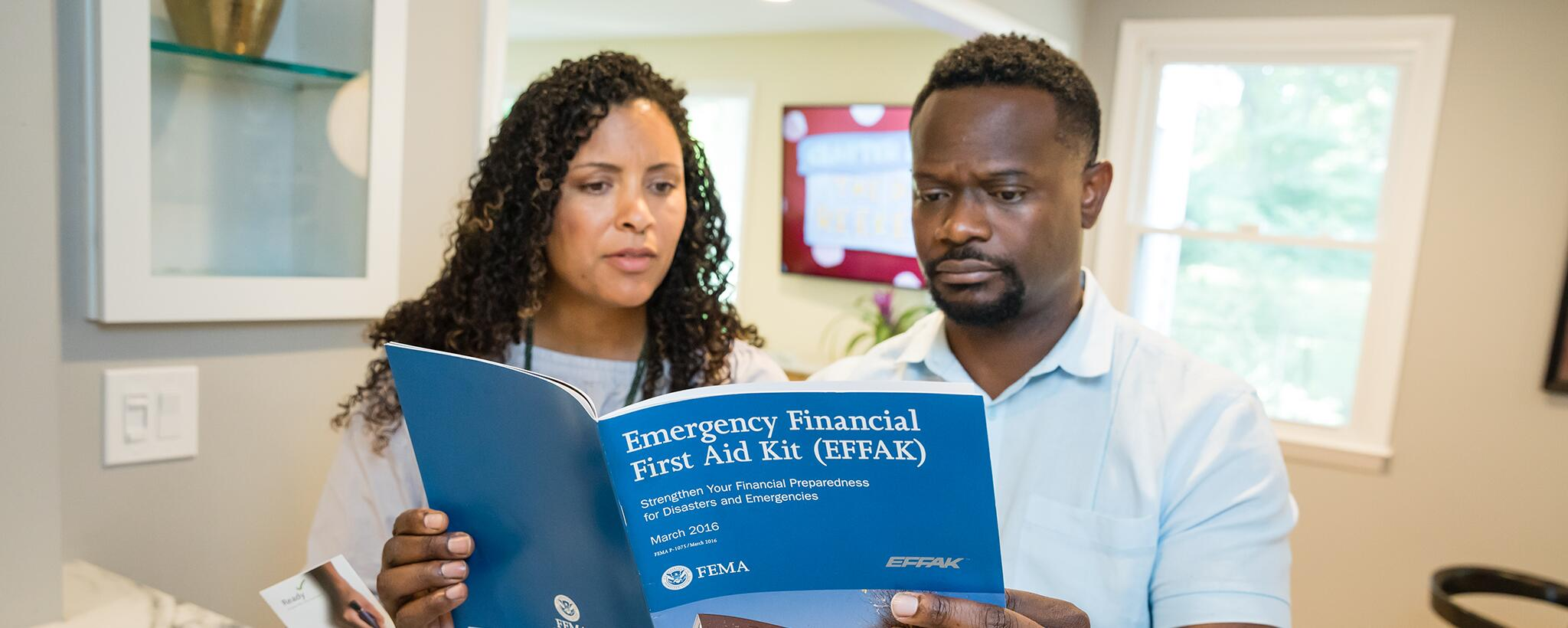 a couple looks at an Emergency Financial First Aid Kit