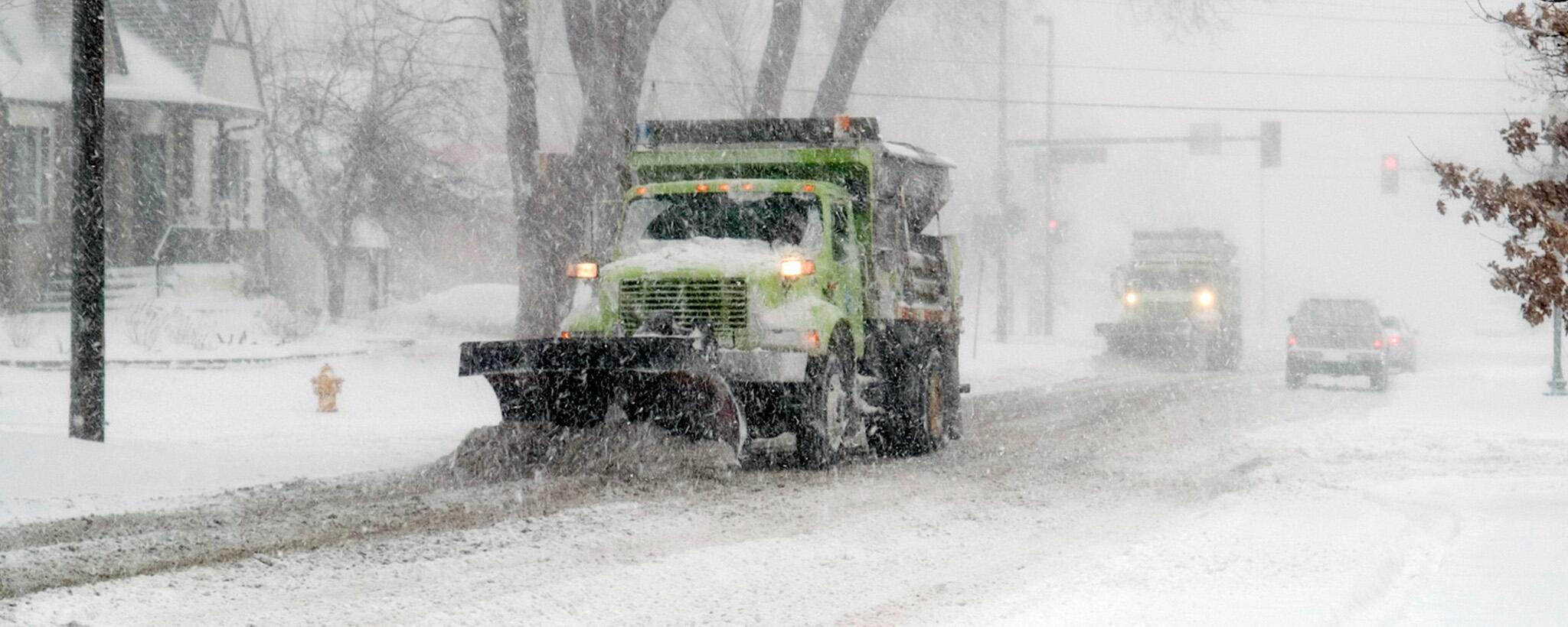 plow clears snow during a storm