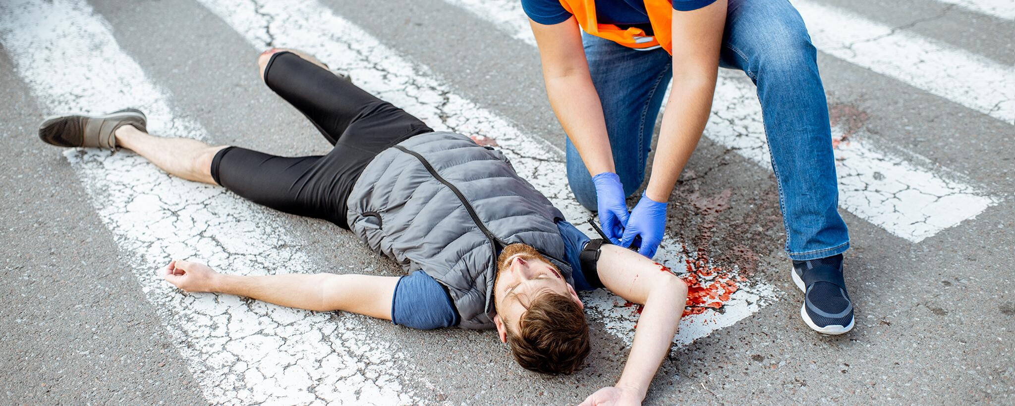 a man performs first aid on an injured person laying on road