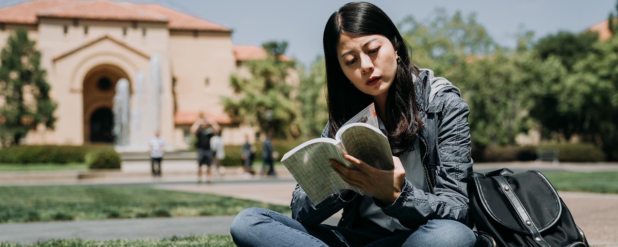 a college student reading a book on campus