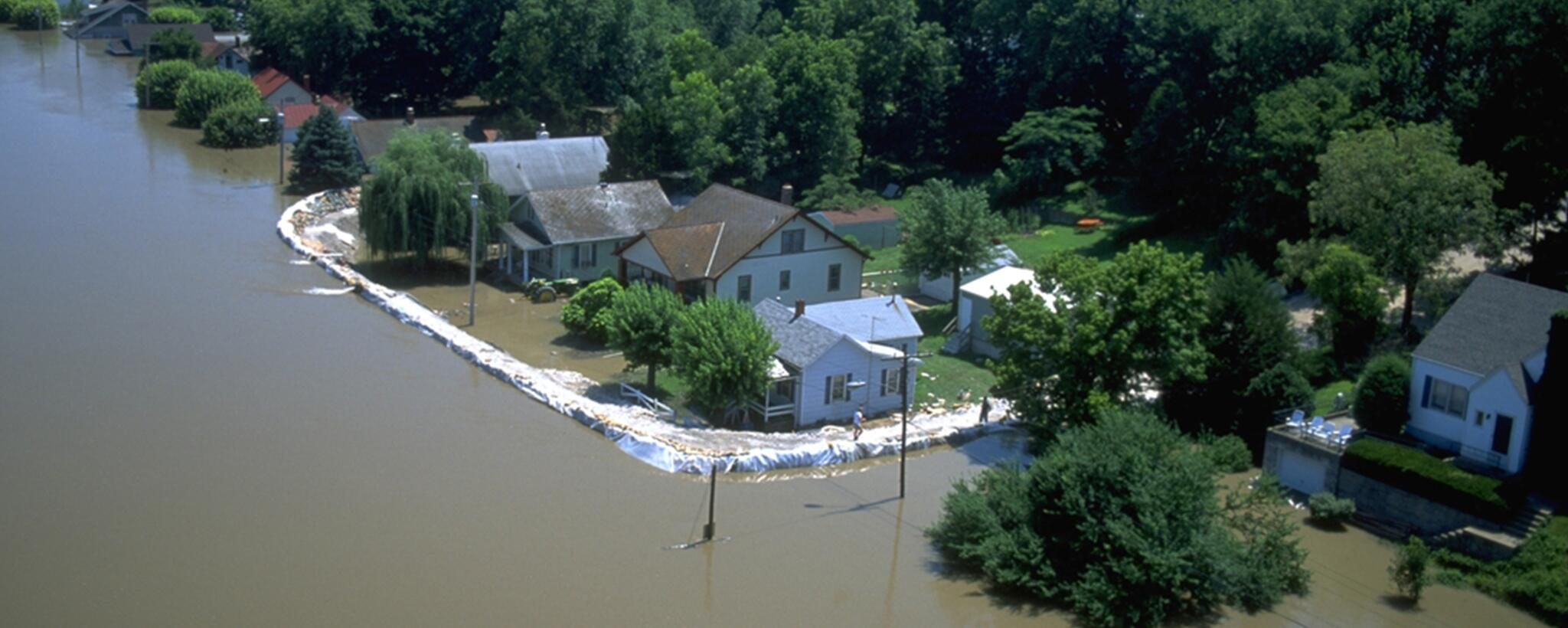 a house protected from flood waters by a barrier of sand bags.