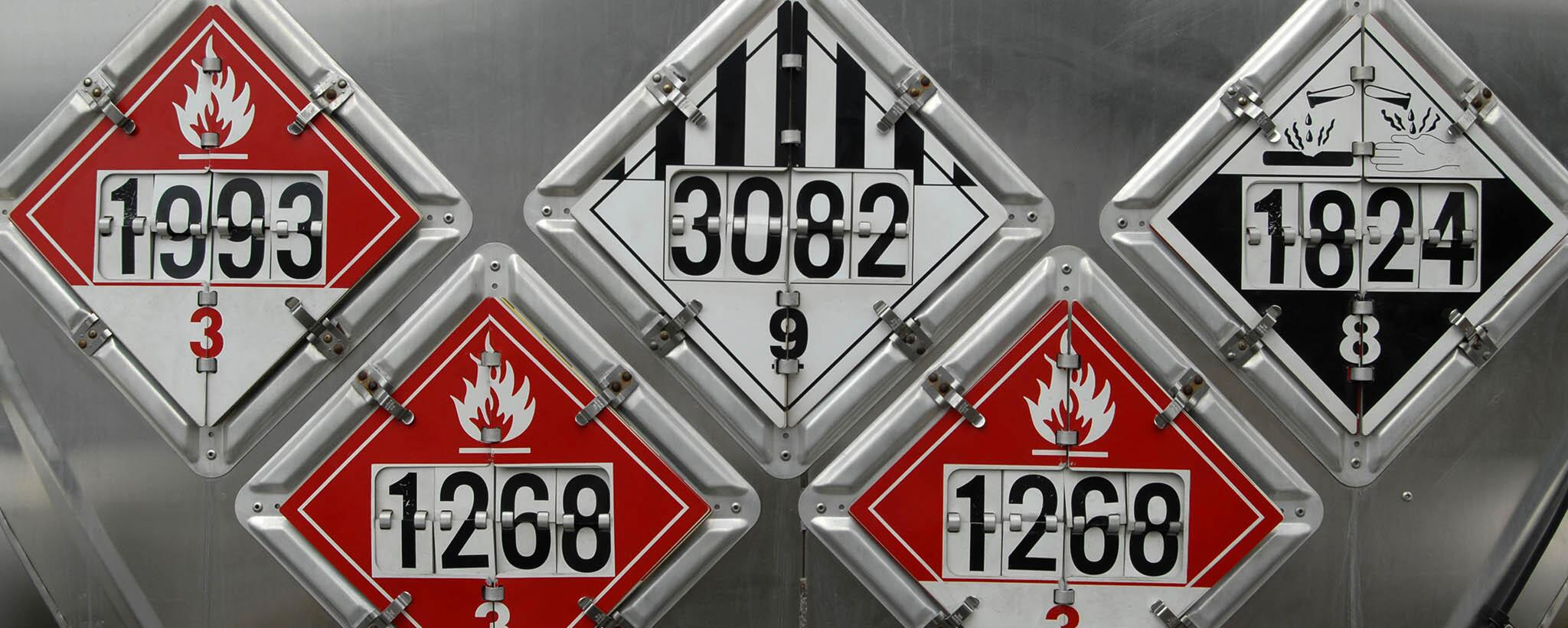 Five different hazardous materials signs showing different numbers and warnings
