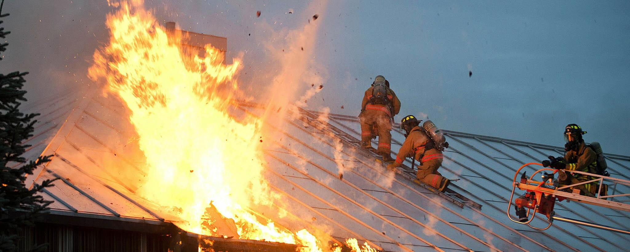 Image of firefighters on flaming roof