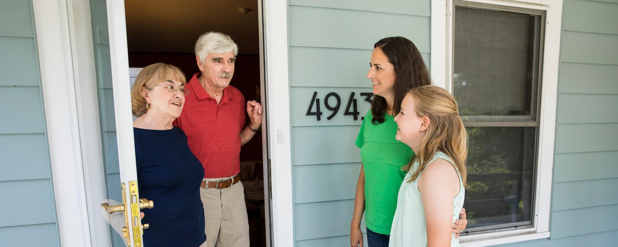 A couple stands at the door talking to their neighbors, a woman and her daughter.