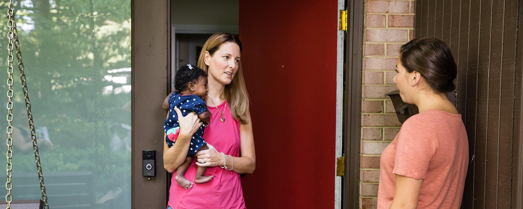 a woman holding an infant talks to her neighbor at the door