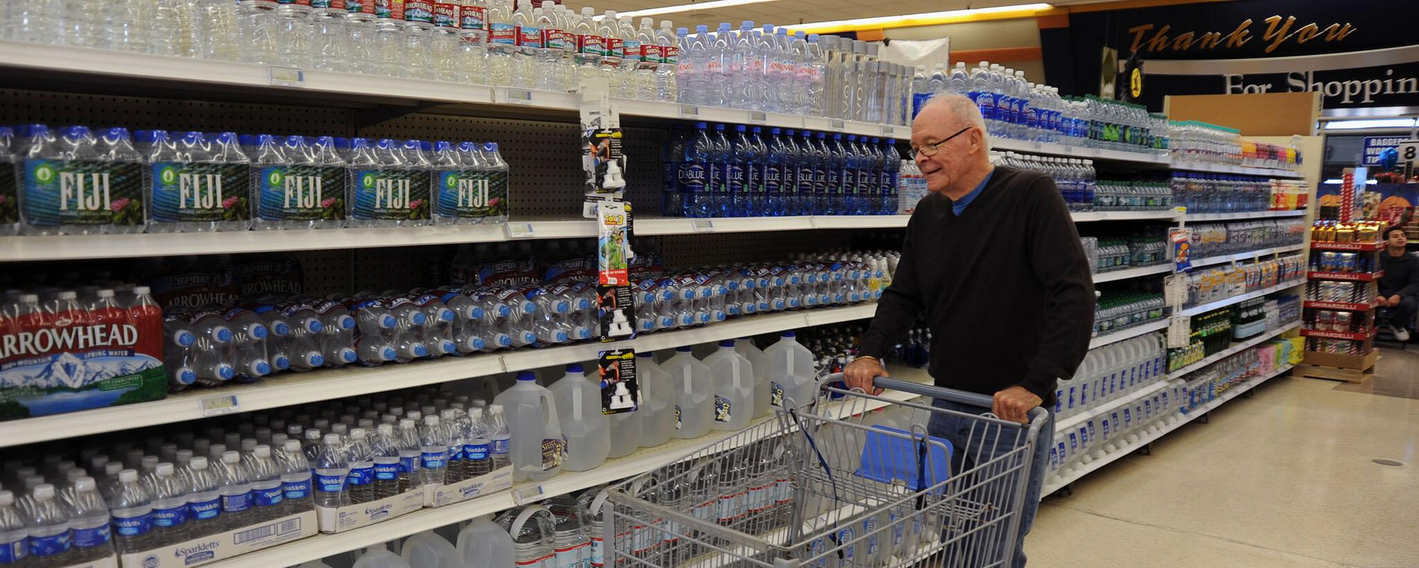 elderly man shops for water