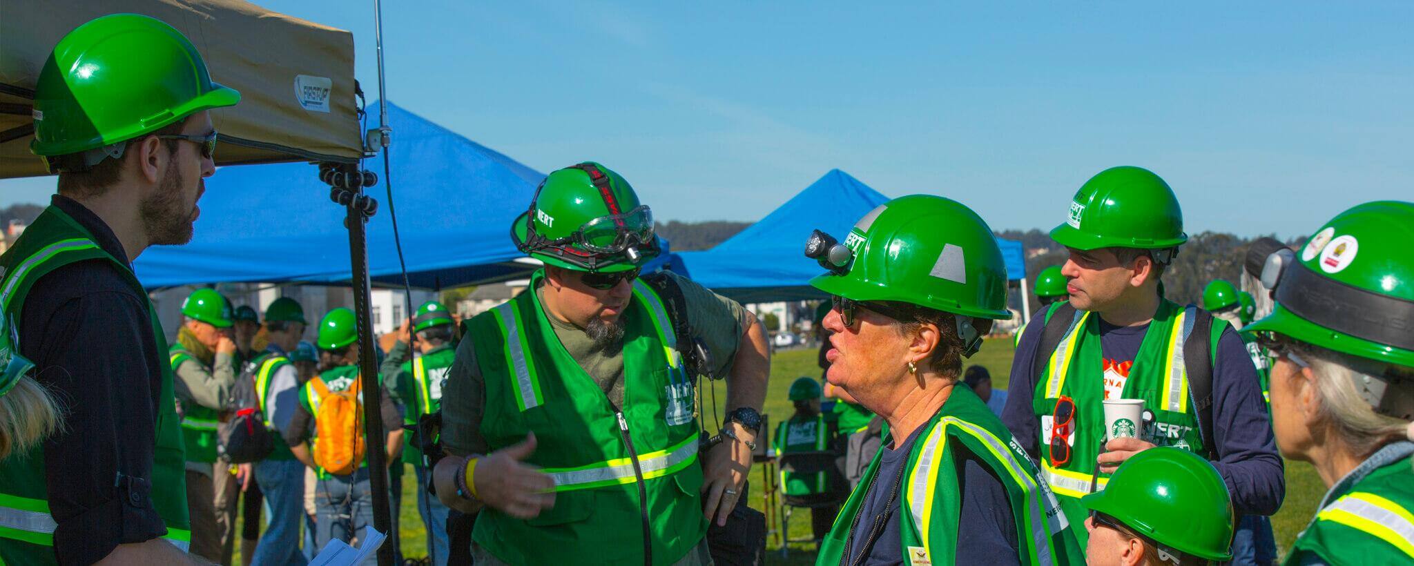 A group of men and women with green hard-hats and vests.