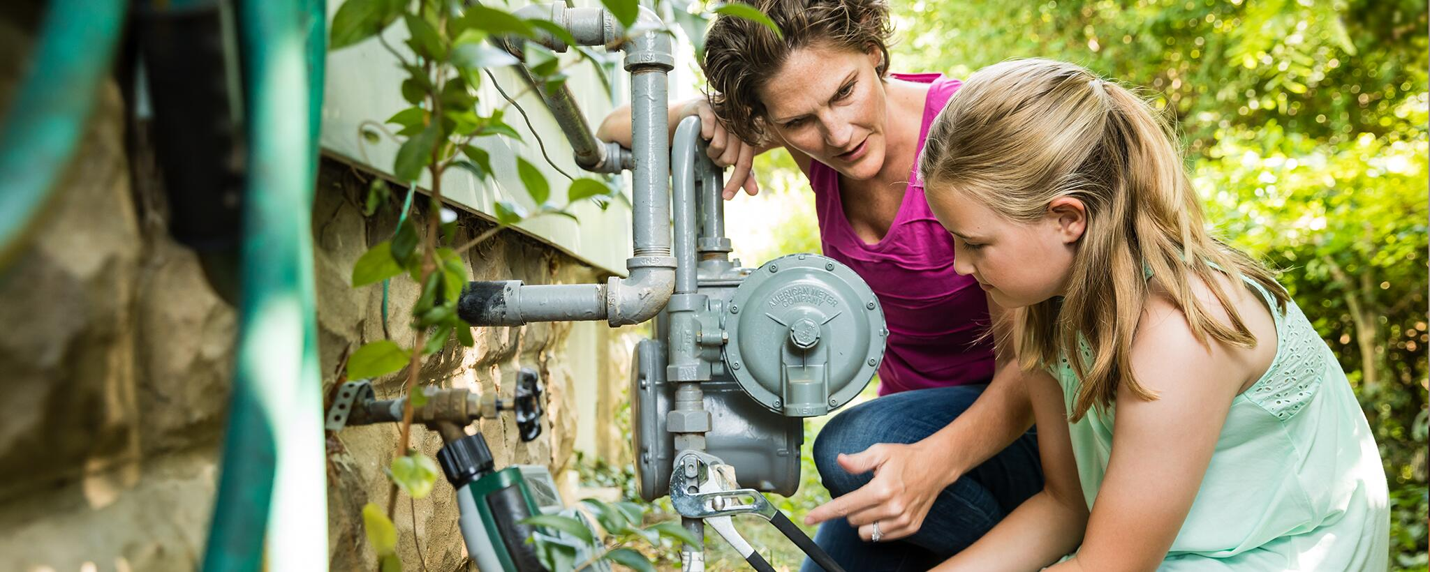 A mother teaches her school-age daughter how to turn off utilities for the house with a wrench.