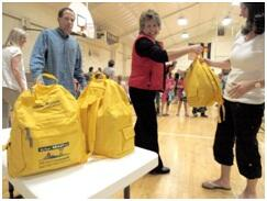 Volunteers pass out emergency kits in yellow backpacks