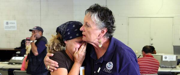 A FEMA worker comforts a disaster victim.