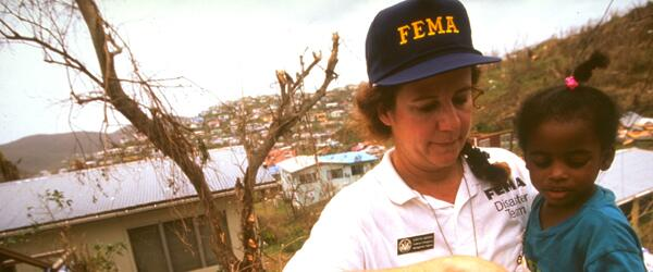 A FEMA worker carrying a child away from disaster area