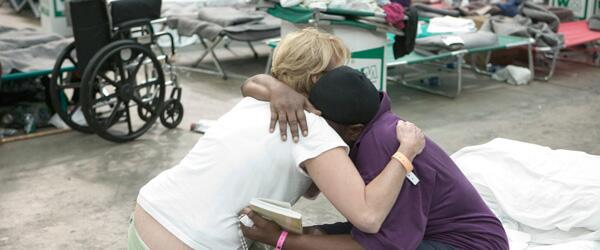An aid worker comforts a Hurricane Katrina disaster victim.