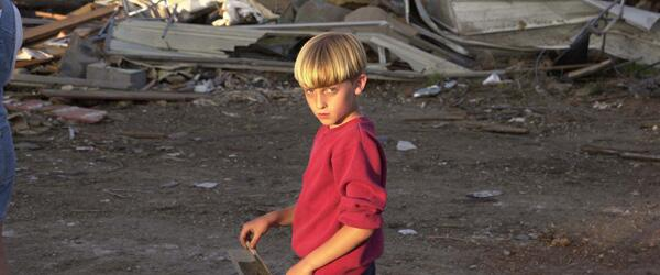 A child walks past the remains of his home which was destroyed by a tornado.