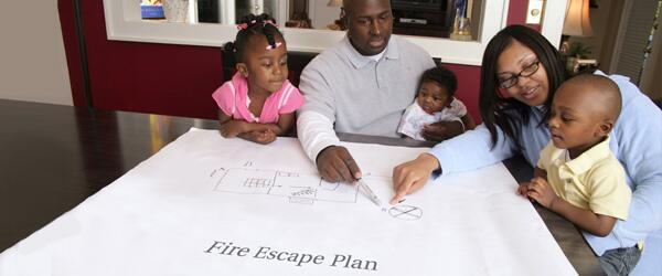 A family with young children makes a fire escape plan.