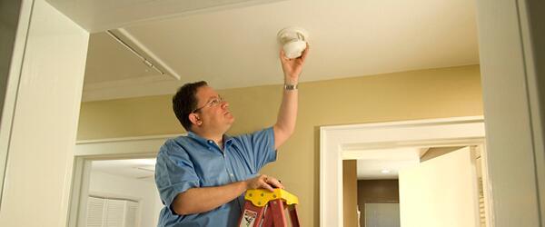 A handyman installs a smoke alarm for an elderly resident.