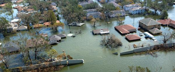 Flood waters pouring through a broken levee into a neghborhood of houses