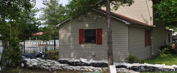 A home with sandbags around it with rising flood waters.