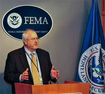 FEMA Administrator Craig Fugate stands at a podium during a press conference.