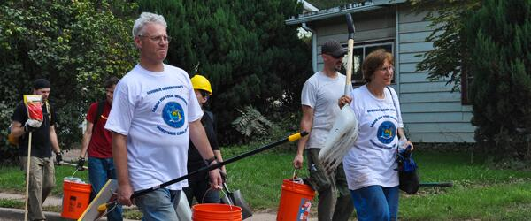 Volunteers in matching t-shirts arrive to aid in disaster clean-up.