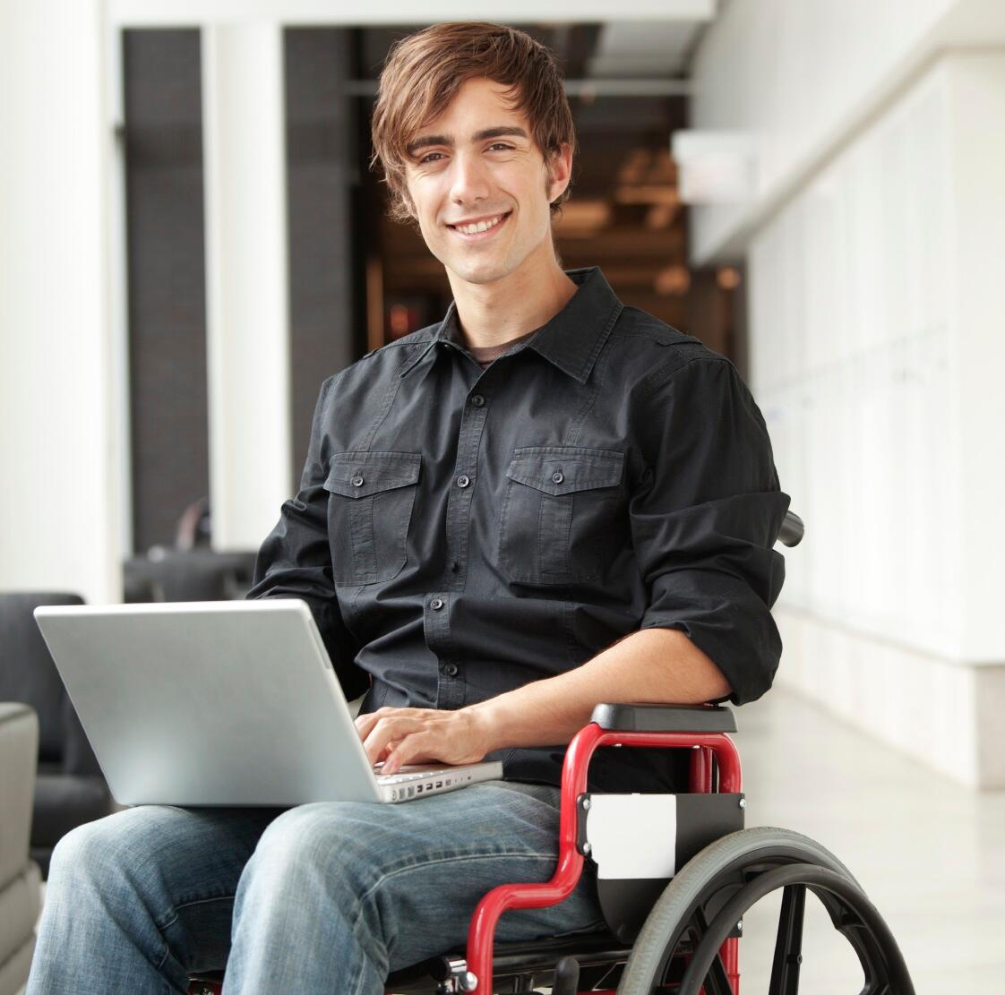 Young man in wheelchair on laptop