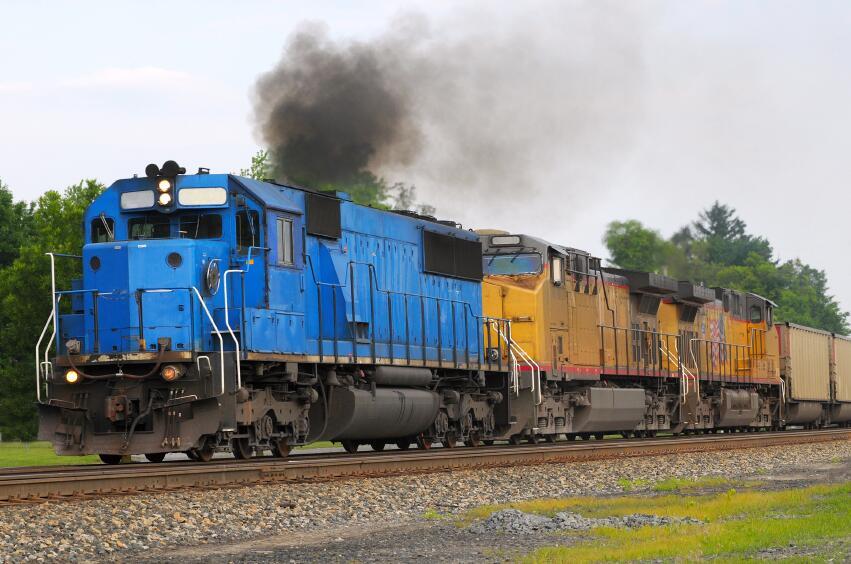 Train engine running down the track spewing dark smoke
