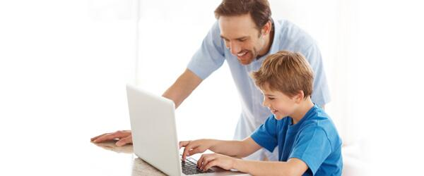 Father teaching his son on a laptop computer