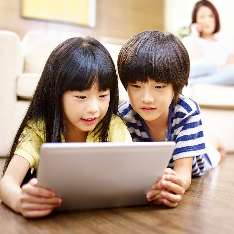 two kids looking at a laptop