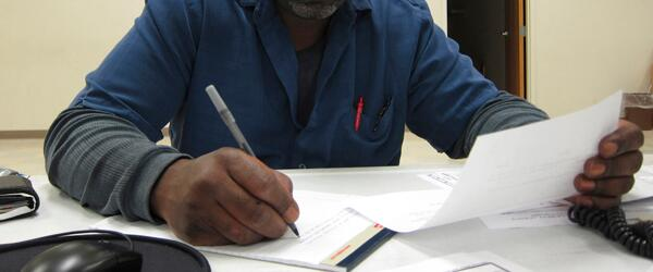 A man filling out Federal assistance paperwork.