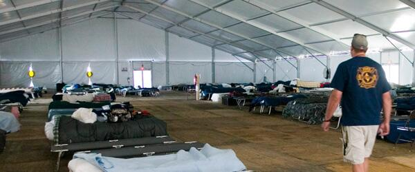 A mass care shelter with rows of cots