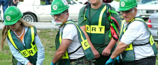 "People wearing green hard-hats and green-vest saying ""CERT"", volunteers for a CERT Team, working to clean up"