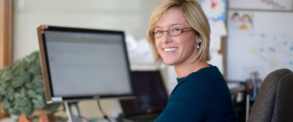 A smiling woman sitting at a computer