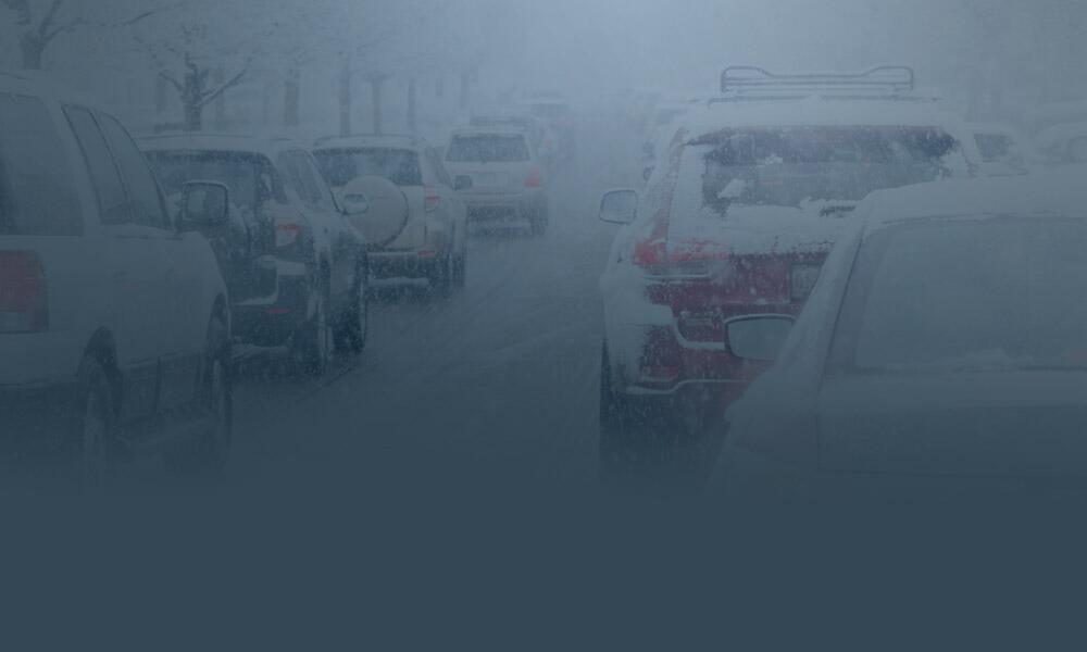 Two rows of snow-covered cars move slowly along the highway in heavy traffic during a snow storm.