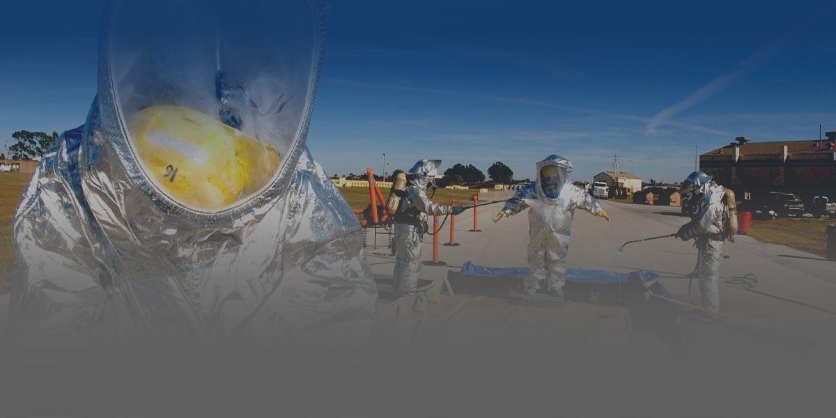 Foto de un equipo de profesionales especializados en el manejo de materiales peligrosos en una carretera limpiando sus uniformes
