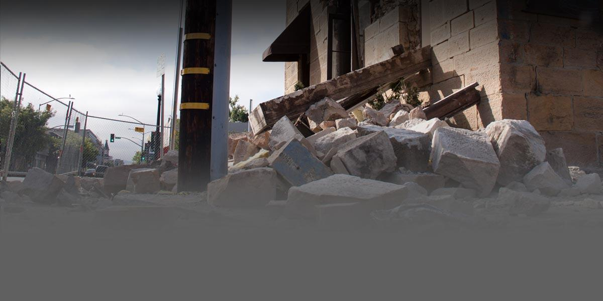 Photo of rubble and debris on the ground next to a damaged building that sustained structural damage from an earthquake.