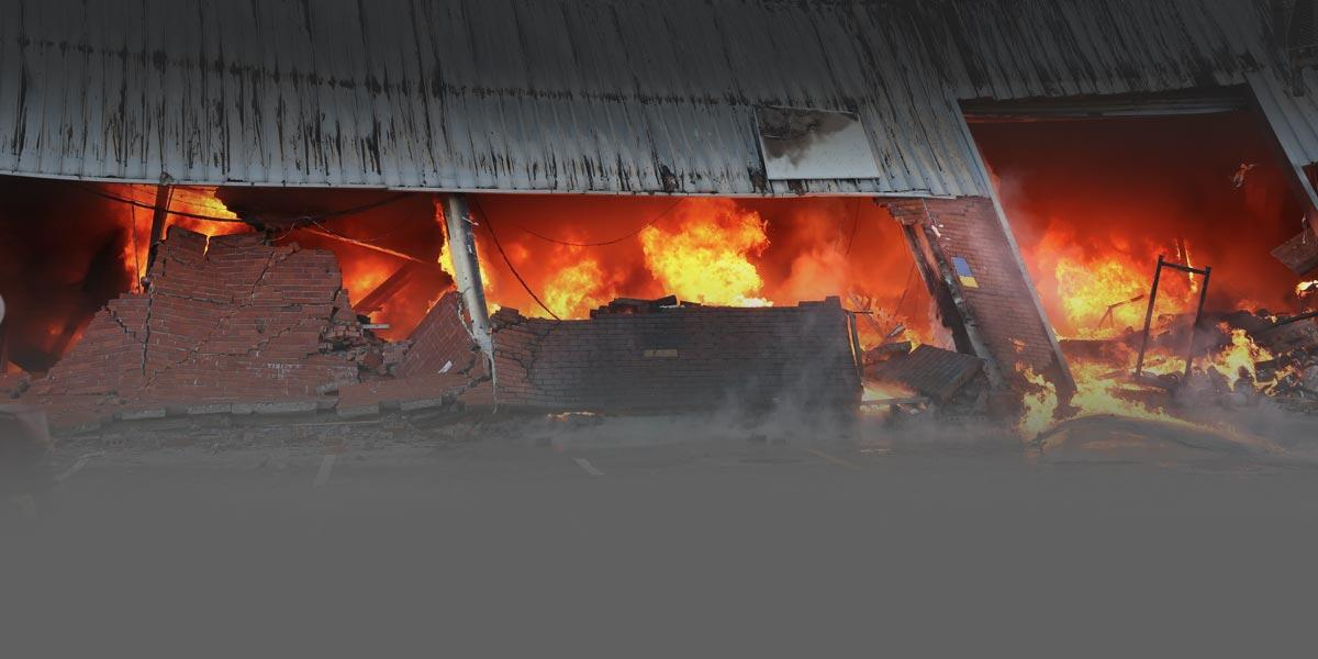 Photo of a burning warehouse building with a fire blazing inside.