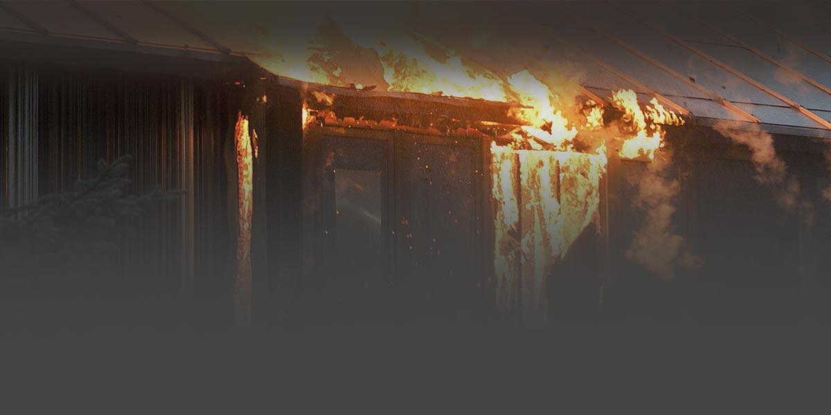 Foto de una casa cubierta en llamas en el exterior.