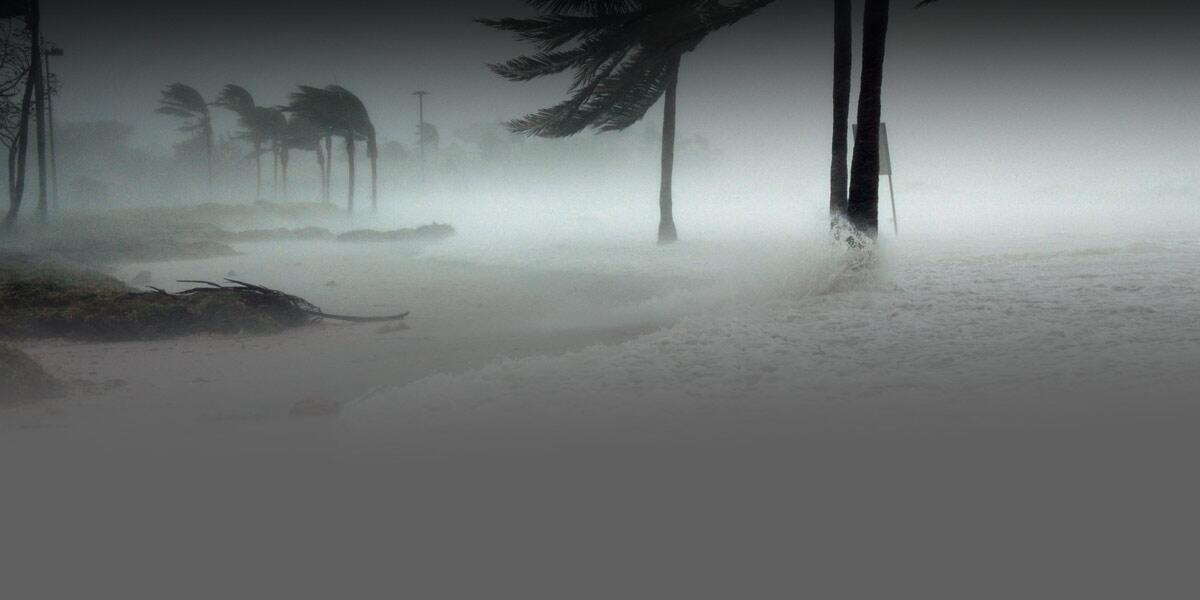 Photo of a beach causing partial flooding into a street along with heavy rain and the wind.