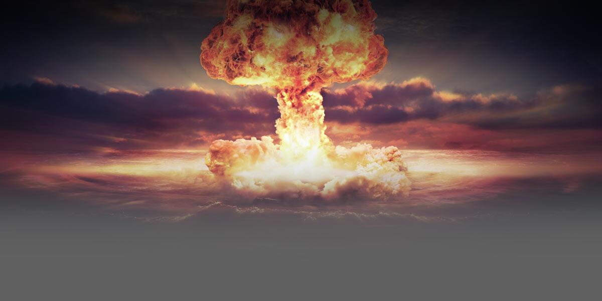 Gráfica de una explosión nuclear con una nube en forma de hongo que se extiende sobre un terreno abierto.
