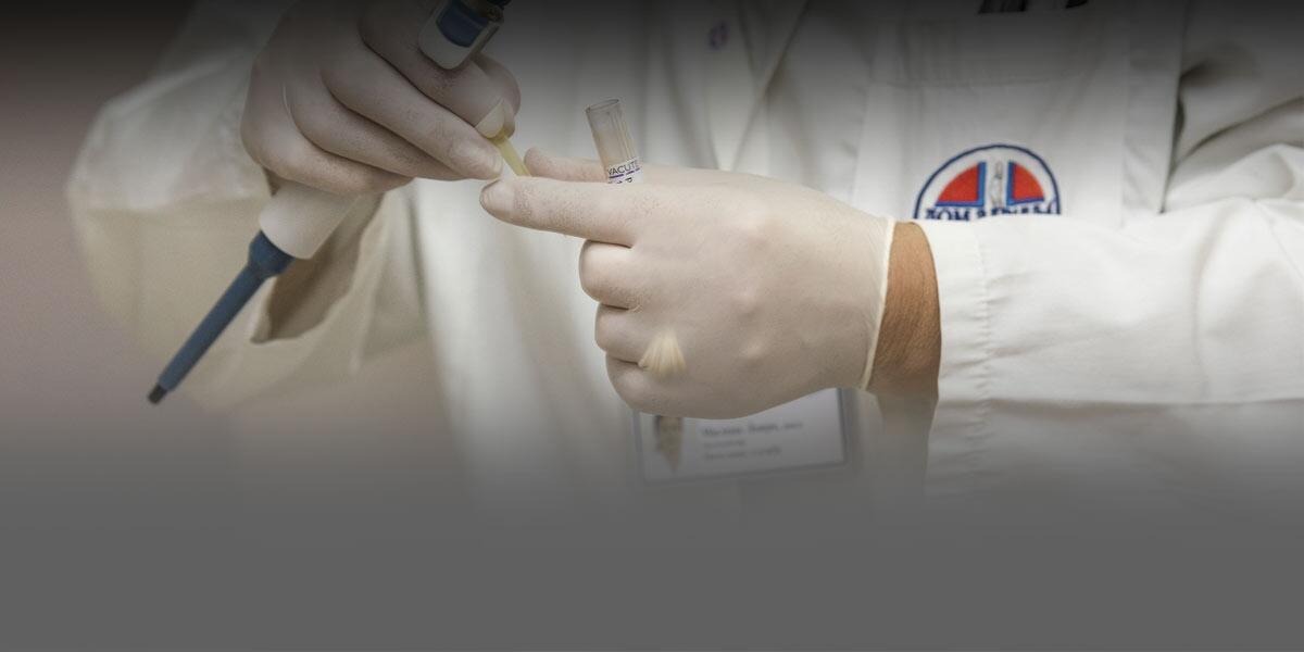 Foto de un médico tapando un tubo de ensaye.