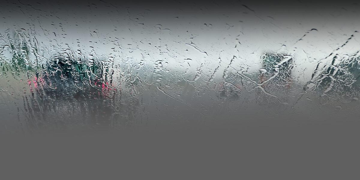 Photo of a car's interior windshield fully wet on the outside driving during a rainstorm.