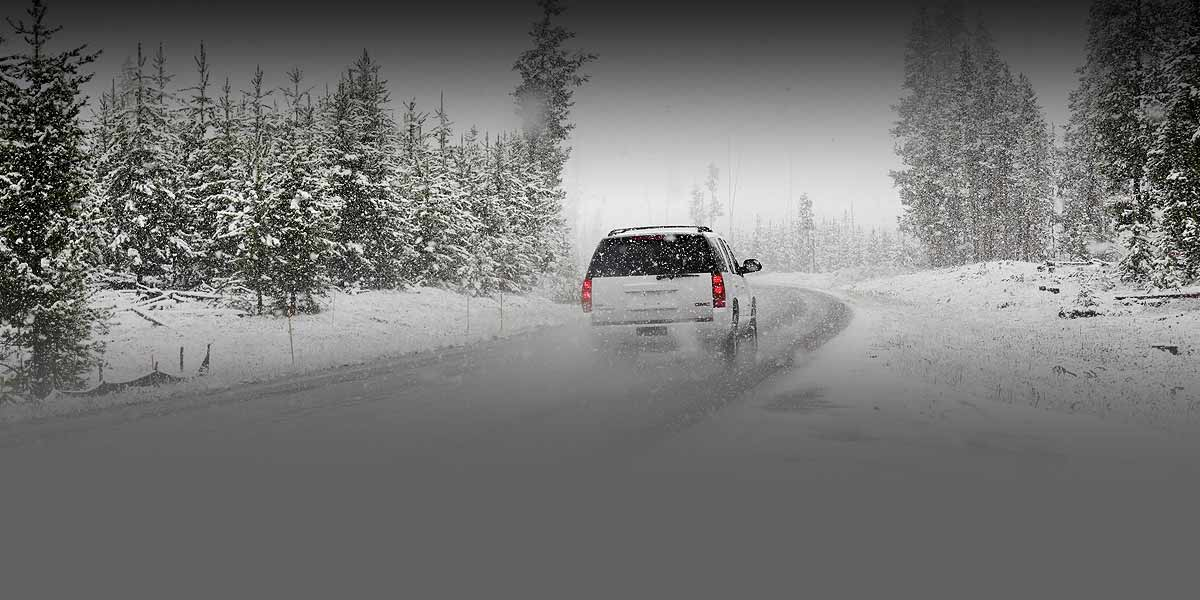Photo of an SUV driving on a road during a snowstorm.
