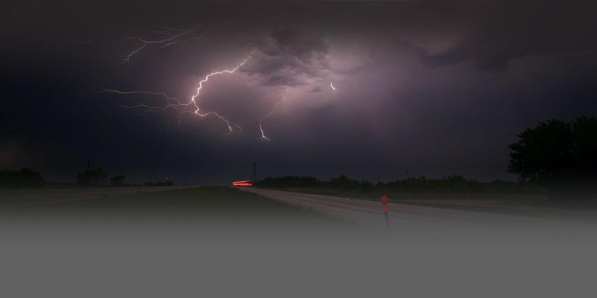 Foto de una tormenta eléctrica con relámpagos en un paisaje abierto en la noche.