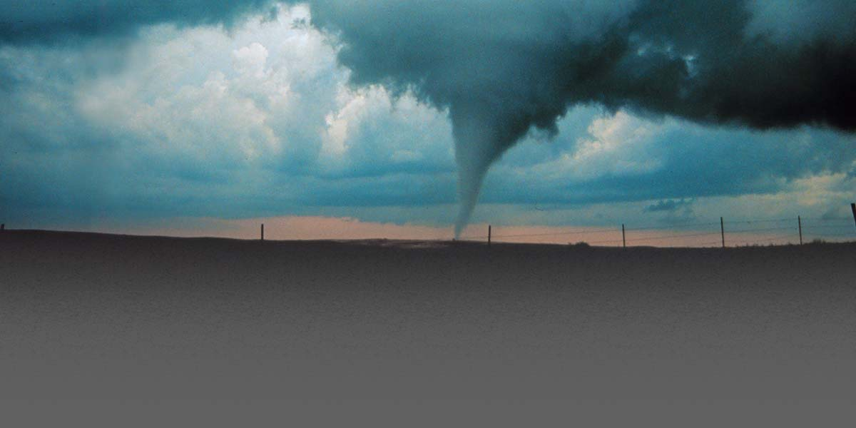 Photo of a tornado in an open landscape at late afternoon.