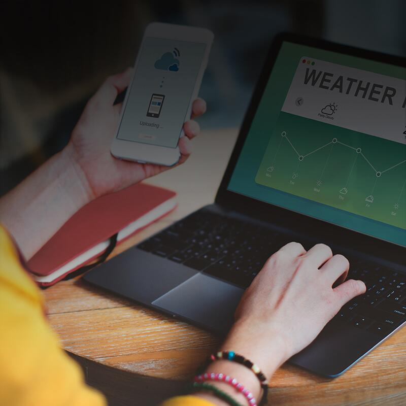 a photo of a woman wearing a yellow sweater looking at weather alerts on her computer and smart phone.