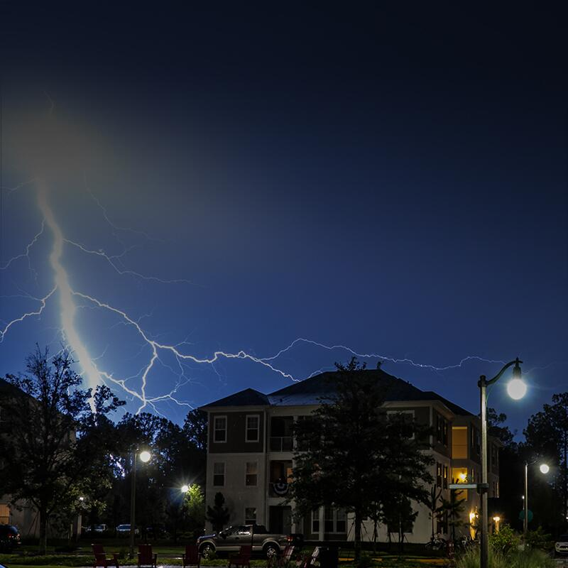 Image shows a lightning bolt striking in the background of an apartment building.