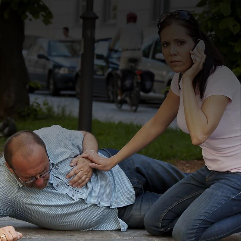Photo of a man lying on the ground having a heart attack, while a woman on her cell phone tries to help him.