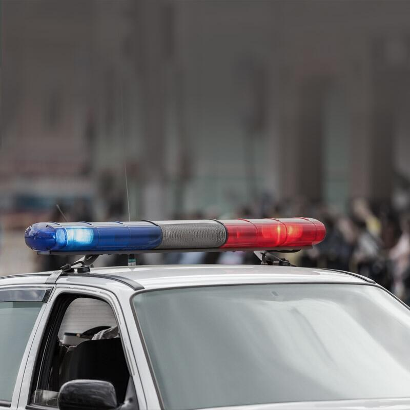 Photo of the top of a parked police car with its sirens on.