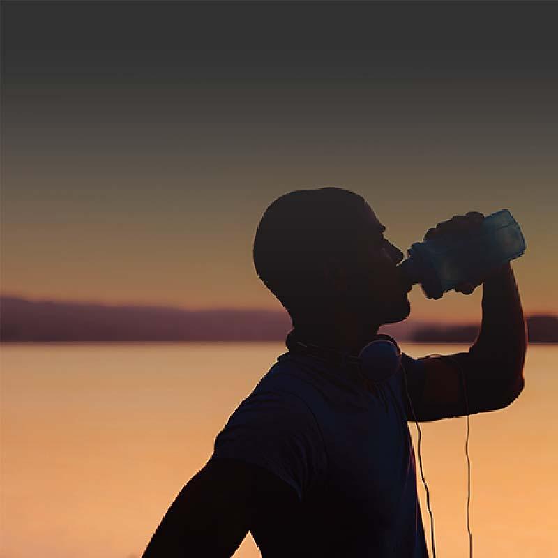 Foto de una silueta de un hombre en mangas cortas quien está de pie y bebiendo agua en un día caluroso cuando el sol se está met